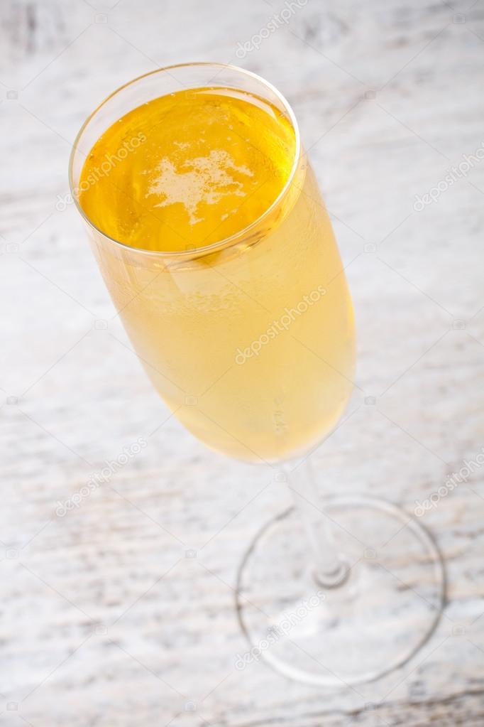 Glass of champagne on wood table — Stock Photo #13133376
