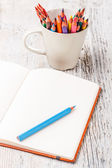 Note and color pencils — Stock Photo