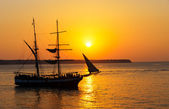 Sunset with sailing ship — Stock Photo