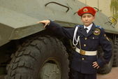Young cadet with an armored troop carrier — Stock Photo