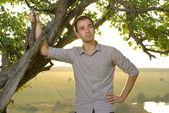 Guy under tree on field — Stock Photo