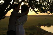Couple under tree at summer evening — Stock Photo