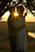 Couple kissing under tree at evening — Stock Photo