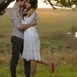 Foto de Stock  : Two sweethearts kissing under tree on field
