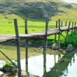 Old wooden bridge over river — Stock Photo #43797227