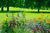 Chaise lounge for recreation near flowerbed — Foto Stock
