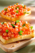Bruschetta on wooden board — Stock Photo