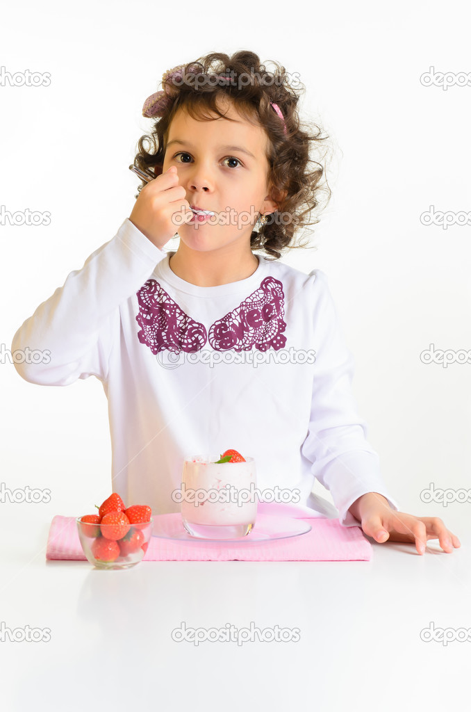 Little girl, 8 years old, eating yoghurt with strawberry — Stock Photo #17128931