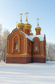 Orthodox Church in a snowy field — Stock Photo