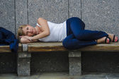 Young woman tired businessman lying on a bench a hard day on the background of a modern business center — Stock Photo