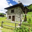 Stone house in the Alpine shepherds village in the Italian Alps of summer meadows — Foto Stock