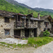 Stone house in the Alpine shepherds village in the Italian Alps of summer meadows — Stock Photo