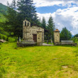 The stone church in the village cemetery in the Alps. Italy — Stock Photo