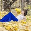 A young girl on the edge of an autumn forest with a bouquet of autumn leaves — Stock Photo