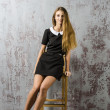 Beautiful young girl in a black dress and long hair brown hair sitting on a chair — Stock Photo