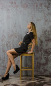 Beautiful young girl in a black dress and long hair brown hair sitting on a chair — Fotografia Stock