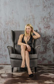 Beautiful young slender girl in a black evening dress sitting in a chair and having fun — Foto Stock