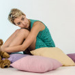 Cheerful girl with short hair in a jacket and skirt summer lying on pillows and playing with teddy bear — Stock Photo #40355973