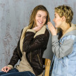 Two young girlfriends discuss something and laughing — Stock Photo