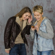Two young girlfriends discuss something and laughing — Stock Photo #40357921