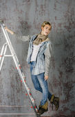 Young girl in jeans and jacket standing on the stairs stepladder and flirts — Stock Photo