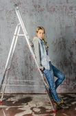 Giovane ragazza in jeans e la giacca in piedi sulla scala scale e flirta — Foto Stock