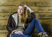 Young beautiful girl with long hair in leather jacket and jeans — Stock Photo