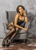 Beautiful young mulatto woman in black lingerie and stockings — Stock Photo