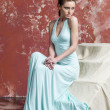 Young beautiful brown-haired woman in blue light silk dress with open shoulders and a long skirt goes upstairs — Stock Photo #42242243