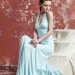 Young beautiful brown-haired woman in blue light silk dress with open shoulders and a long skirt goes upstairs — Stock Photo