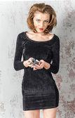 Belle jeune femme brune dans une robe bleue avec ouvrir les épaules et tenant une poignée de jetons pour casino — Photo