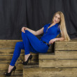 Beautiful long haired blonde in blue overalls and high heels sitting on wooden stairs — Stock Photo #48586873