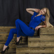 Beautiful long haired blonde in blue overalls and high heels sitting on wooden stairs — Stock Photo #48586877