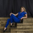 Beautiful long haired blonde in blue overalls and high heels sitting on wooden stairs — Stock Photo #48586879