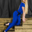 Beautiful long haired blonde in blue overalls and high heels sitting on wooden stairs — Stock Photo #48586923