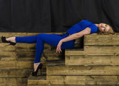 Beautiful long haired blonde in blue overalls and high heels sitting on wooden stairs — Stock Photo