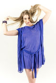 Beautiful long-haired blonde in a clear blue tunic and blue shoes — Стоковое фото