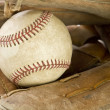 A baseball ball on a glove with black background — Foto Stock