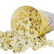 Popcorn in a container spilled on white — Stock fotografie