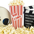 Movie Clapper Board in popcorn with film reel isolated on white — Stock Photo