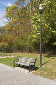 Lavička v klidném parku — Stock fotografie