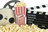 Movie Clapper Board in popcorn with film reel isolated on white — Stok fotoğraf