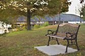 Nice bench in a morning green park by lake — Stock Photo