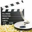 Movie Clapper Board in popcorn with film reel isolated on white — Stockfoto