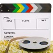 Stock Photo: Movie Clapper Board in popcorn with film reel isolated on white