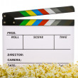 Movie Clapper Board in popcorn with film reel isolated on white — Stock Photo #14933263