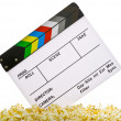 Movie Clapper Board in popcorn with film reel isolated on white — Stock Photo #14933273
