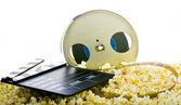 Film reel in popcorn isolated on white — Stock Photo