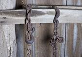 Rusty chain hanging in barn — Stock Photo