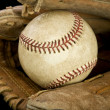 Worn leather baseball glove holding a baseball — Stock Photo